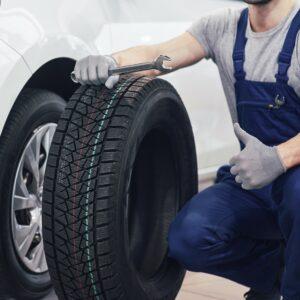 Mann hält neuen Reifen vor einem Auto