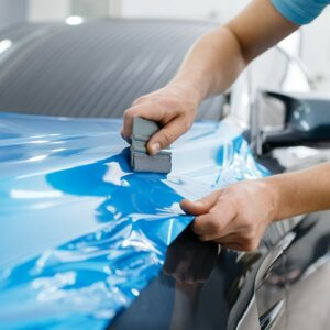 Auto wird von einer Person in Blau foliert