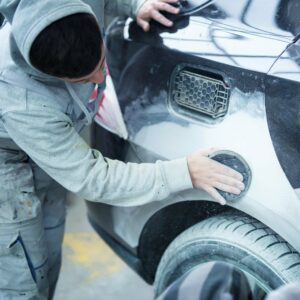 Mann schleif den Kotflügel eines Autos